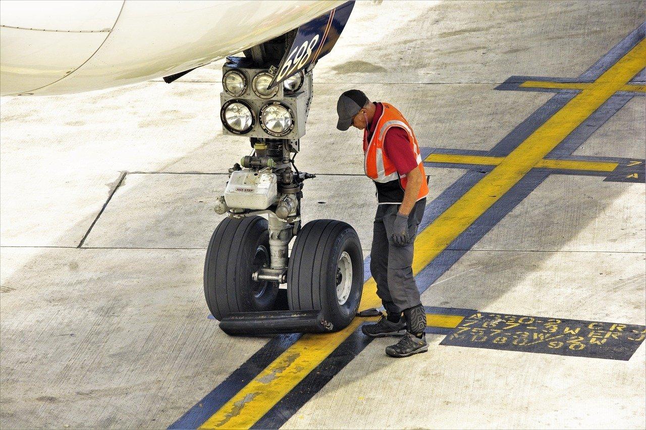 man inspecting landing gear